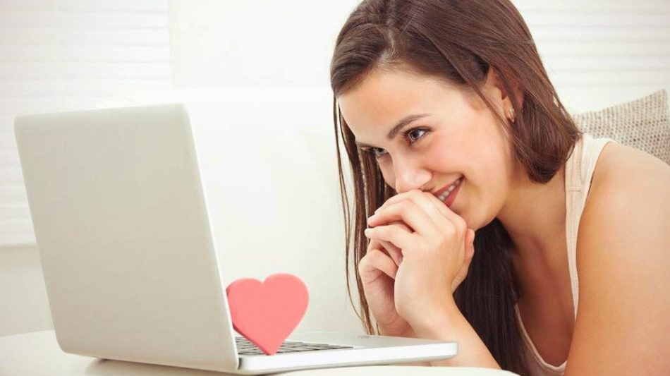 Девушка смотрит на ноутбук