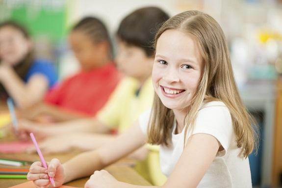 Девочка рисует карандашом и улыбается