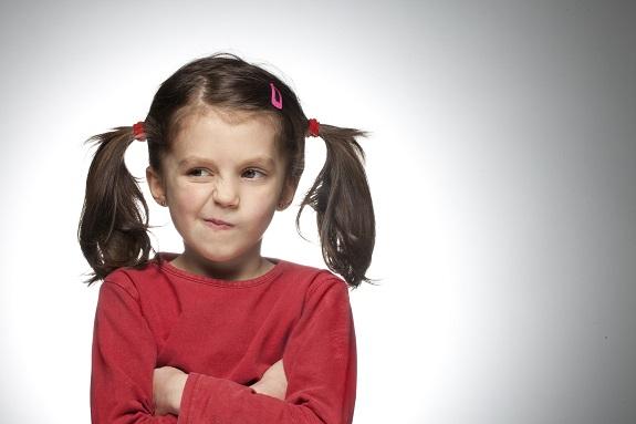 Маленькая девочка  в красной кофте, в косичках стоит и кривляется