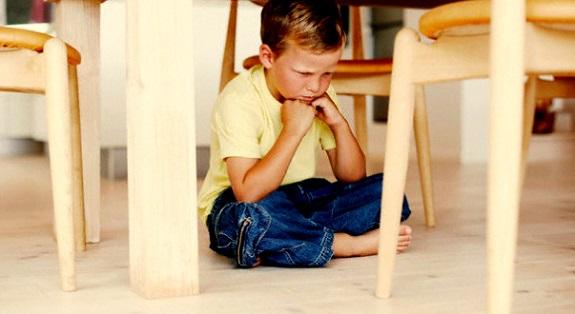 Мальчик сидит скрестив ноги и думает
