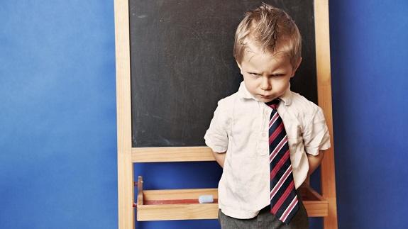 Мальчик у школьной доски стоит и сердито смотрит