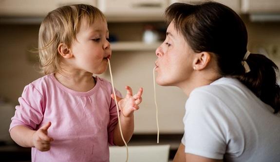 Маленькая девочка и взрослая женщина кушают спагетти