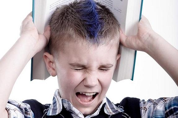 Мальчик с закрытыми глазами  и злостью держит книгу над головой