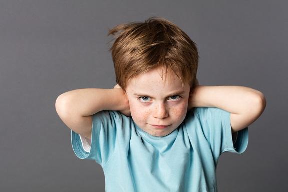 Маленький мальчик с веснушками закрывает уши руками