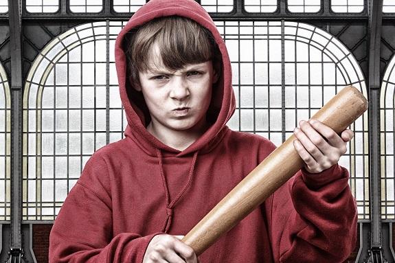 Подросток агрессивно смотрит с битой в руках