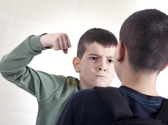 Мальчик подросток сжал кулак и замахнулся рукой на другого мальчика