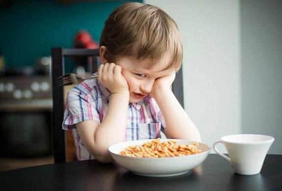 Маленький ребенок сидит за столом подпирая голову руками, перед ним тарелка с едой