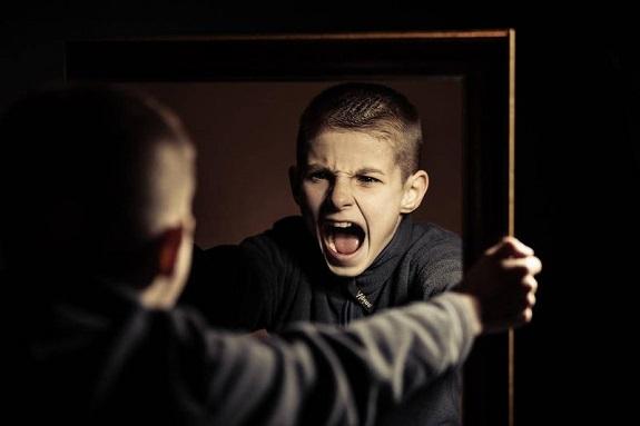 Мальчик смотрит на себя в зеркало и кричит