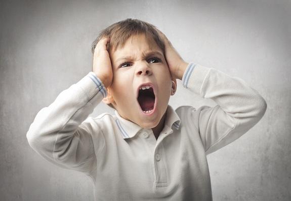 Маленький мальчик кричит и держится за голову руками