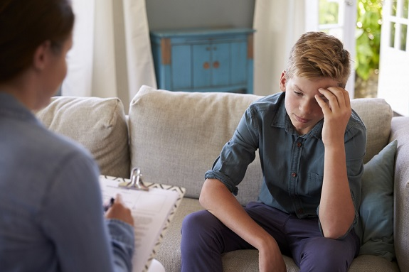 Мальчик держится за голову руками, а рядом сидит женщина
