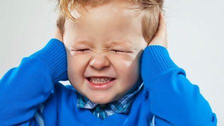 Маленький мальчик в синей рубашке, закрыл уши руками и зажмурил глаза