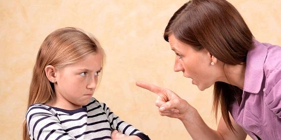 Взрослая женщина сердито смотрит  на маленькую девочку и показывает на нее пальцем