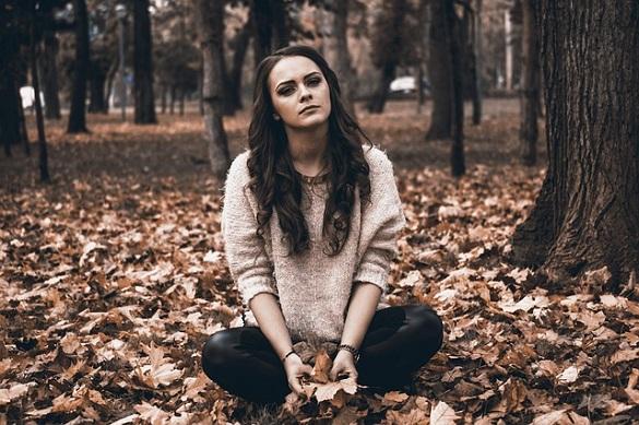 Девушка сидит на улице и держит в руках листья