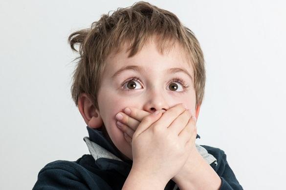 Мальчик подросток прикрывает рот двумя руками