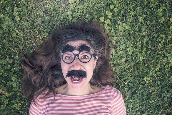 Девушка лежит на траве с наклеенными усами и бровями