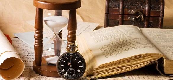На столе лежит книга и часы