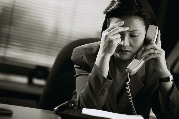 Женщина разговаривает по телефону и держится за голову