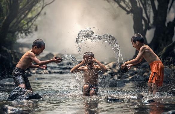 Трое мальчиков обливают друг друга водой в озере