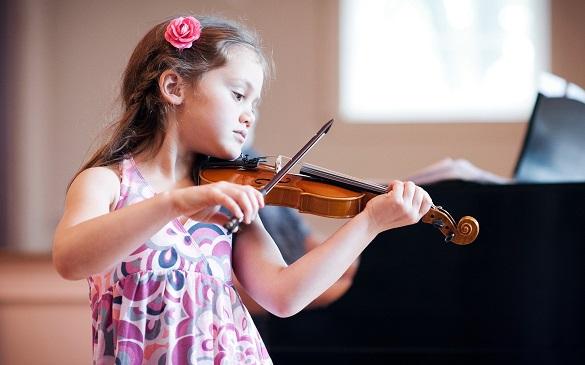 Маленькая девочка держит в руках скрипку
