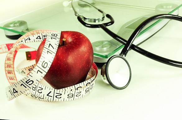На фото яблоко и весы