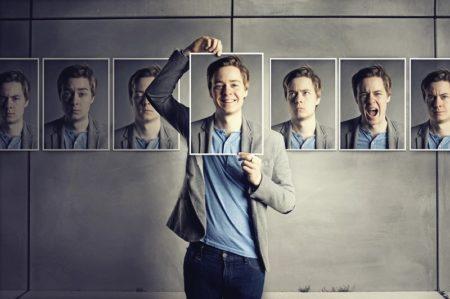 Мужчина прикладывает фотографии к лицу