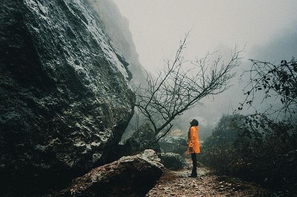 Девушка стоит возле скалы и смотри вверх