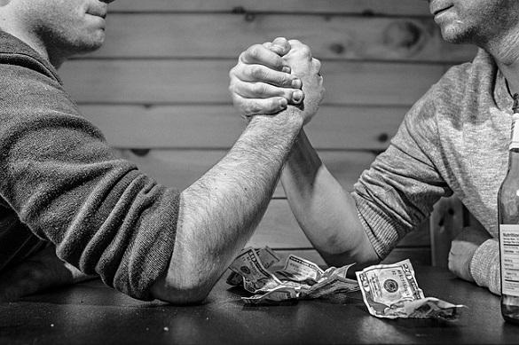 Двое мужчин соревнуются на руках, возле них лежат деньги