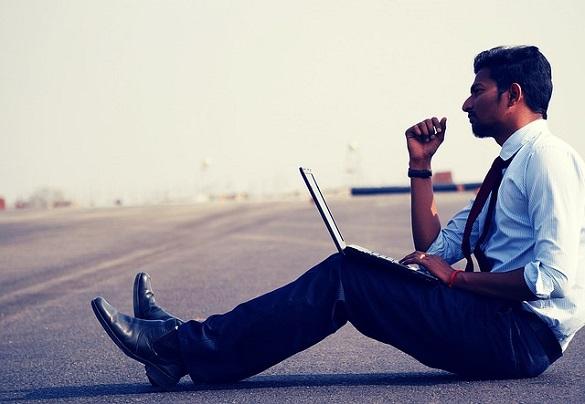 Мужчина сидит на дороге с ноутбуком
