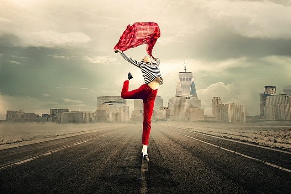 Девушка прыгает на дороге