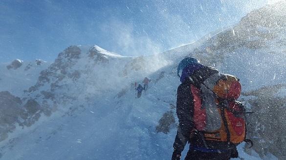 Человек поднимается в горы зимой