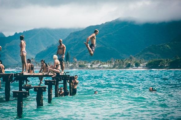 Люди прыгают в воду с пирса