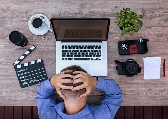 Мужчина держится за голову, перед ним ноутбук, чашка кофе, цветок, фотоаппарат, блокнот, ручка