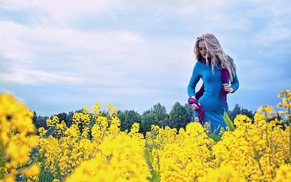 Женщина стоит возле цветов