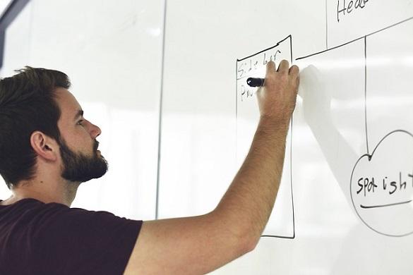 Мужчина что-то рисует на доске фломастером