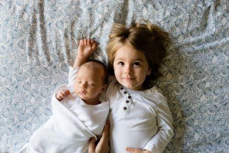 Двое детей лежат на кровати