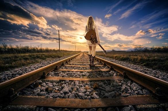 Девушка с гитарой идет вдоль рельс