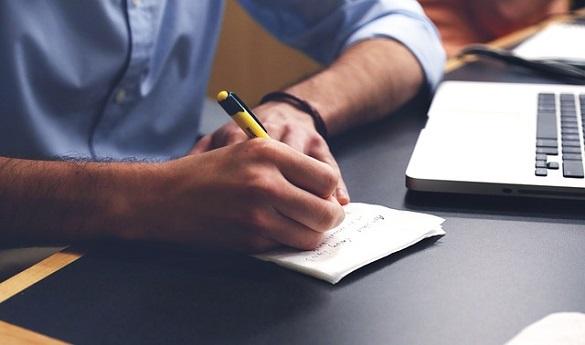 Мужчина пишет ручкой на листе бумаге