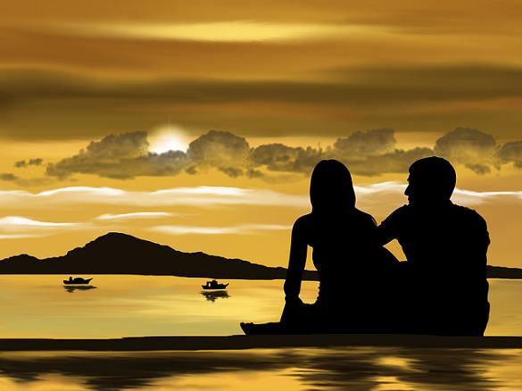 Мужчина и девушка сидят на фоне заката