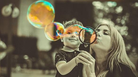 Ребенок с женщиной надувают пузыри