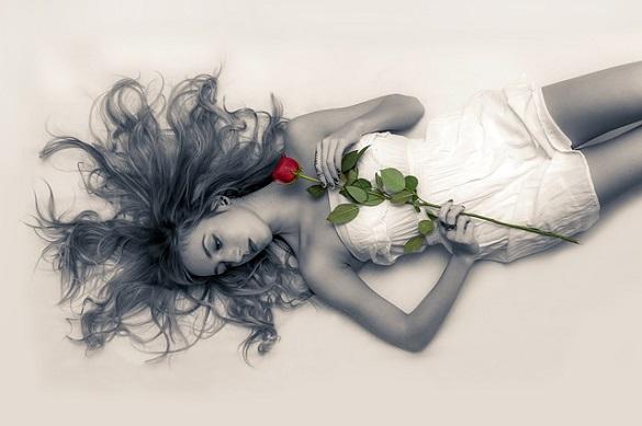 Девушка лежит держа в руках розу